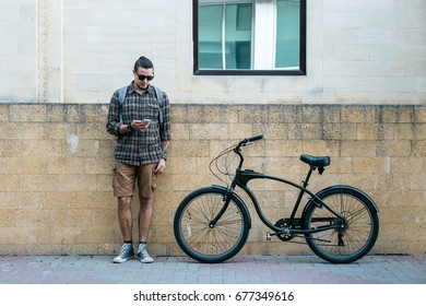Handsome Young Man Cyclist Standing Next To Bike And His Looking At Smartphone. Street Lifestyle Urban Everyday Concept