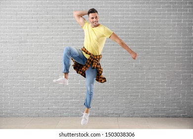 Handsome young man dancing against brick wall