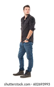 Handsome young man in dark grayish plaid shirt looking back over shoulder. Full body length portrait isolated over white studio background.
