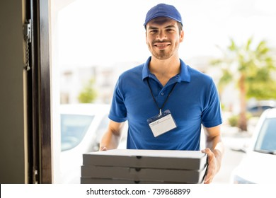 Handsome young man delivering a few boxes of pizza to the front door with a smile