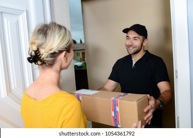handsome young man delivering a parcel to young woman at home