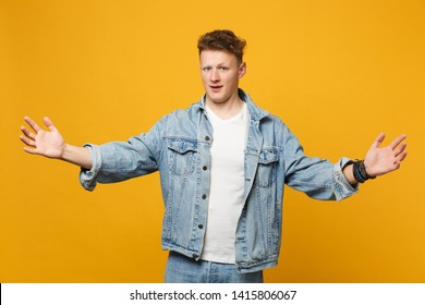 Handsome young man in denim casual clothes gesturing demonstrating size with horizontal workspace isolated on yellow orange background. People sincere emotions, lifestyle concept. Mock up copy space