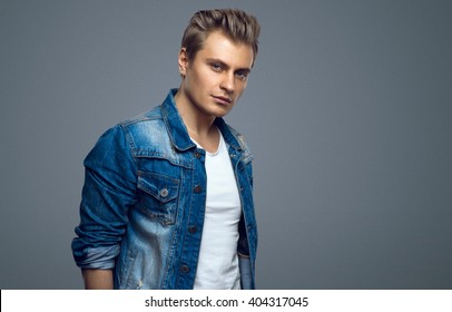 Handsome young man in a denim jacket. Fashionable man. Brutal sexy guy looking at the camera. Studio shoot