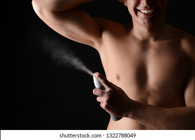 Handsome young man with deodorant on dark background