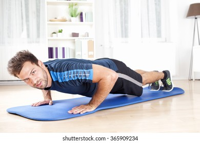 Handsome Young Man Doing Daily Push Up Exercise at Home, Looking at the Camera