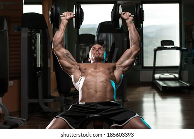 Handsome Young Man Doing Dumbbell Incline Bench Press Workout In Gym