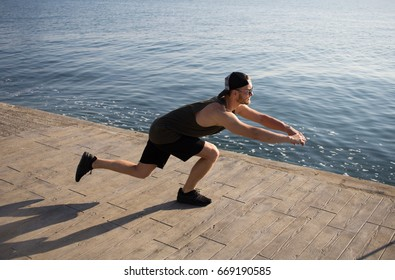 Handsome young man doing exercises outdoors in summer time, fit male training fitness. Handsome man in sunglasses