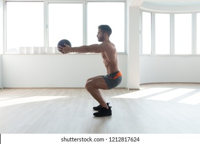 Handsome Young Man Doing Squad With Medicine Ball As Part Of Bodybuilding Training