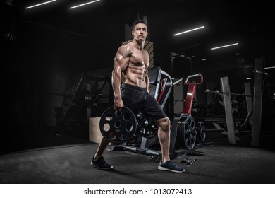 Handsome young man doing weightlifting exercises in the gym, squats, development of leg muscles.