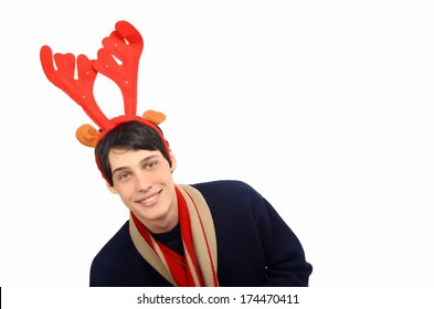 Handsome young man dressed for Christmas, wearing reindeer horns.  Isolated on white.