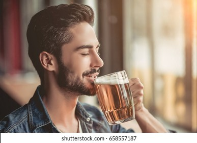 Handsome young man is drinking beer in bar