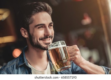Handsome young man is drinking beer in bar and smiling