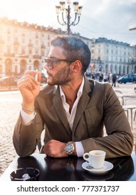 Handsome young man drinking espresso coffee and smoking cigarette, wearing elegant coat posing at table outside on urban background.
