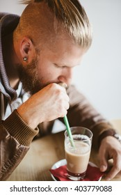 handsome young man drinking healthy shake in coffee shop
