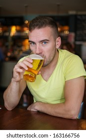 Handsome young man drinking light beer in a pub