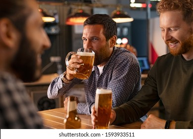 Handsome young man drinking a pint of draft beer in bar with friends. Happy friends sitting in a pub and talking over cold drinks. Mid adult friends enjoying together a night while guy take a sip.