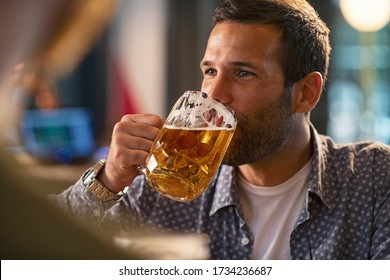 Handsome young man drinking a pint of beer. Cheerful mid man in casual clothing feeling relaxed while enjoying draft beer in bar. Middle aged guy take a sip from his drink at pub during the night.