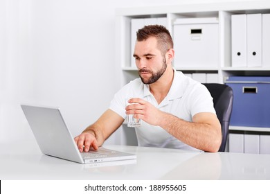 Handsome young man drinking water from a glass of in the office