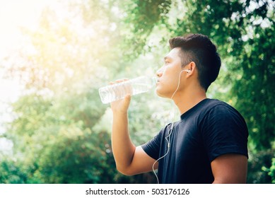 Handsome Young man drinking water from a bottle After Training.