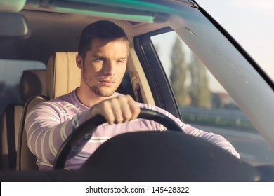 Handsome young man driving a car holding the right hand on the wheel