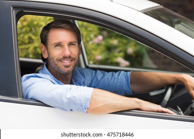 Handsome young man driving his car and smiling. Happy young man sitting in the car and looking at camera. Portrait of a man driving rental car.
