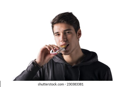 Handsome young man eating cereal bar, looking at camera standing, isolated on white background