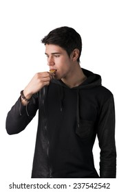 Handsome young man eating cereal bar, looking away standing, isolated on white background