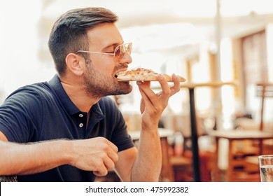 Handsome young man eating a slice of pizza in cafe