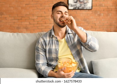 Handsome young man eating tasty potato chips at home