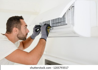 handsome young man electrician cleaning air filter on an indoor unit of air conditioning in a client house