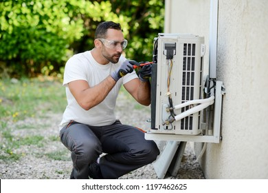 handsome young man electrician installing an air conditioning in a client house