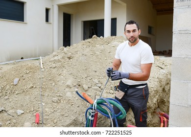 handsome young man electrician wiring cable outdoor in a house building construction site