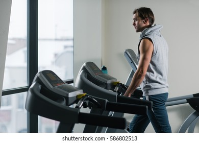 A handsome young man exercising on a treadmill at the gym