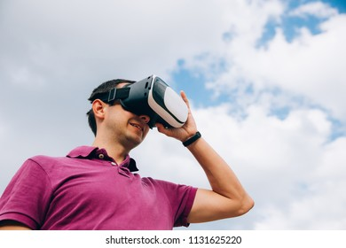Handsome young man experiencing virtual reality via VR headset outdoors.