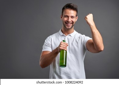 A handsome young man feeling happy and celebrating while holding a beer