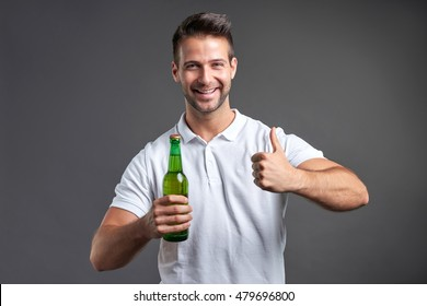A handsome young man feeling happy showing thumbs up and holding a bottle of beer