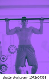 handsome young man in fitness gym lifting up and hanging while working on hands and back muscles duo tone