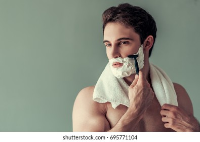 Handsome young man with foam on his face is shaving using a razor, on gray background