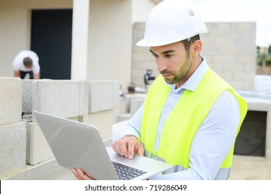 handsome young man foreman architect supervising a new house construction site