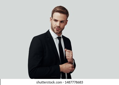 Handsome young man in formalwear looking away and adjusting sleeve while standing against grey background