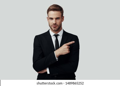 Handsome young man in formalwear looking at camera and pointing copy space while standing against grey background