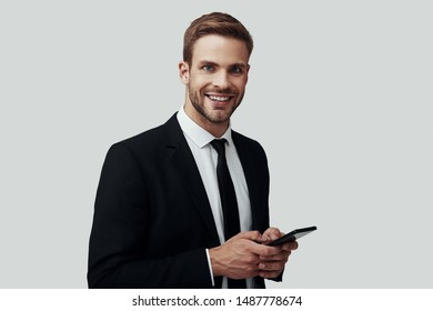 Handsome young man in formalwear using smart phone and smiling while standing against grey background