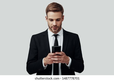 Handsome young man in formalwear using smart phone while standing against grey background