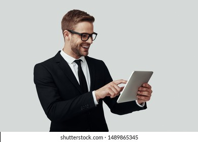 Handsome young man in formalwear working using digital tablet and smiling while standing against grey background
