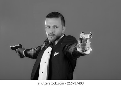Handsome young man gangster police spy agent assissin holding and pointing with two guns wearing a suit black and white portrait