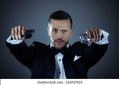 Handsome young man gangster police spy agent assissin holding and pointing with two guns wearing a suit