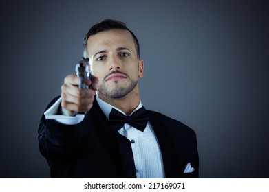 Handsome young man gangster police spy agent assissin holding and pointing a gun wearing a suit