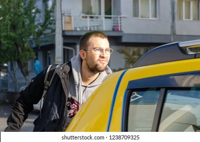A handsome young man getting in to a taxi .He is sad.