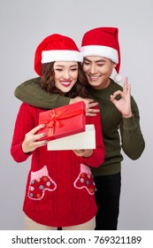 Handsome young man giving present to beautiful woman. Christmas time.