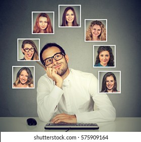 Handsome young man in glasses working on computer wondering thinking which beautiful woman he likes loves the most